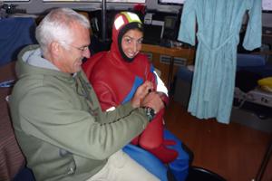 Yves aide Alex à se préparer. Elle porte la combi de survi, dite sèche, qui permet de ne pas avoir froid dans les eaux très fraîches de là-bas.